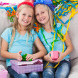 Foto Stock: Cute twins unwrapping their birthday present