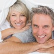 Couple smiling under the covers — Stock Photo