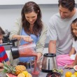 Woman with family pouring fruit from a blender — Stock Photo #28055269