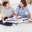 Happy woman and her husband looking at their house plans — Stock Photo