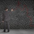 Rear view of a businessman writing a red line through black maze — Stock Photo