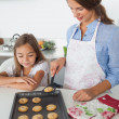 Mother giving a homemade cookie to her daughter — Stock Photo