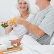 Mature couple clinking their orange juice glasses — Stock Photo