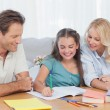 Parents helping her daughter doing her homework — Stockfoto