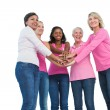 Women wearing breast cancer ribbons with hands together and smil — Stock Photo