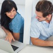 Smiling woman showing something on laptop at her boyfriend — Stock Photo