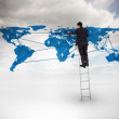 Businessman standing on a ladder drawing a world map — Stock Photo #28055971