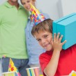 Stock Photo: Little boy shaking his birthday gift