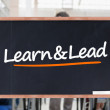 Learn and lead written on blackboard — Stock Photo