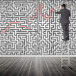 Businessman standing on a ladder solving maze puzzle — Stock Photo #28056519