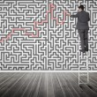 Businessmstanding on ladder solving maze puzzle — Stockfoto #28056519