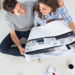 Overview of a husband and his wife holding house plan — Stock Photo
