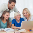 Parents and children using a computer — Stockfoto