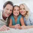 Portrait of a girl and her parents lying on a carpet — Stock Photo #28056661