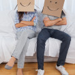 Couple sitting with cardboard boxes on head — Stock Photo