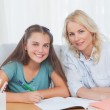 Woman helping her daughter doing her homework — Stock Photo