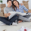Portrait of man and his wife holding house plans — Stock Photo #28056999