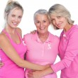 Happy women wearing pink tops and ribbons for breast cancer — Stock Photo #28057091