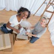 Stock Photo: Pretty friends unpacking boxes in new home