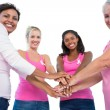 smiling women wearing breast cancer ribbons putting hands togeth — Stock Photo