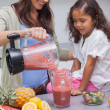 Woman pouring fruit from a blender — Stock Photo