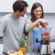 图库照片: Couple putting fruits into blender