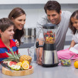 Stock Photo: Smiling family using blender