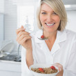 Cheerful blonde eating cereal for breakfast — Stock Photo #28057545