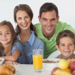 Portrait of parents having breakfast with their children — Stock Photo #28057561