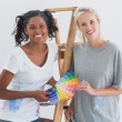 Friendly housemates choosing colour for wall looking at camera — Stock Photo