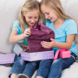 Stock Photo: Young twins unwrapping birthday gift sitting on couch
