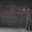 Rear view of a businessman drawing a red line through black maze — Stock Photo #28057983