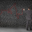 Rear view of businessmdrawing red line through black maze — Stock Photo #28057983