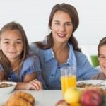 Mother having breakfast with her children — Stock Photo #28058095