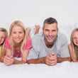 Parents lying in bed with their children — Stock Photo