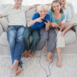 Children playing video games together sitting on the couch — Stock Photo