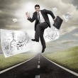 Businessman jumping on a road with drawings floating — Stock Photo #28058231