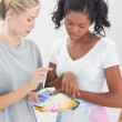 Young housemates choosing colour for wall — Stock Photo