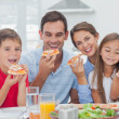 Family eating pizza slices — Stock Photo