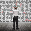 Confused businessman looking at a maze — Stock Photo #28058435