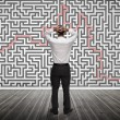 Stock Photo: Confused businessmlooking at maze