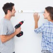 Cheerful man and his wife doing home improvements together — Stock Photo