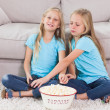 Young twins eating popcorn sitting on a carpet — Stock Photo