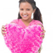 Stock Photo: Little girl showing cushion in the shape of a heart