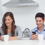 Couple using their smartphones — Stock Photo