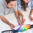 Couple looking at a color chart to decorate their house — Stock Photo