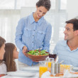 Pretty woman bringing a salad to her family — Stock Photo #28058797