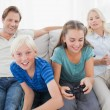 Children playing video games on the couch — Stock Photo #28058875