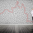 Thoughtful businessmlooking at maze on wall — Stock Photo #28059129