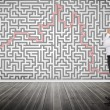Stock Photo: Thoughtful businessmlooking at maze on wall
